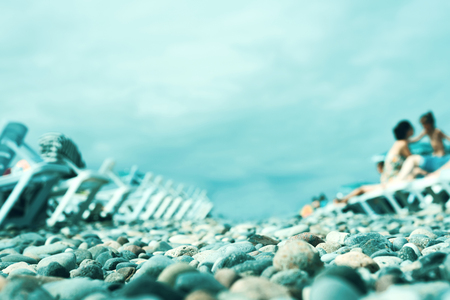 Blurred background of the beach on the Black Sea coast with plastic sunbeds, blue sky on a sunny day Stock Photo