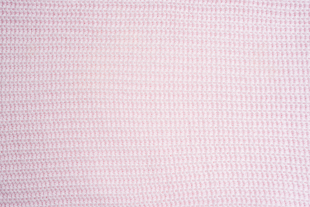 Knitting.Striped  pink  knit fabric texture, knitted pattern background. Bedding with a pink knitted plaid. Copy space. Flat lay, top view
