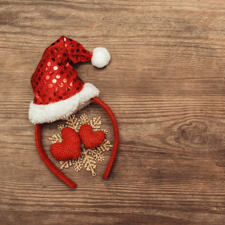 Christmas background with christmas decoration with a red cap of Santa Claus and two hearts on rustic wooden table. Holiday decor concept