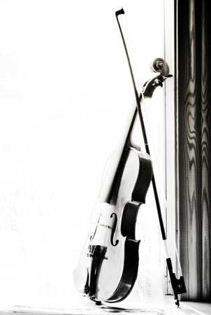 Vertical image of a violin with sheet music  the front of the fiddle on windows background. Black and white photo. Stock Photo