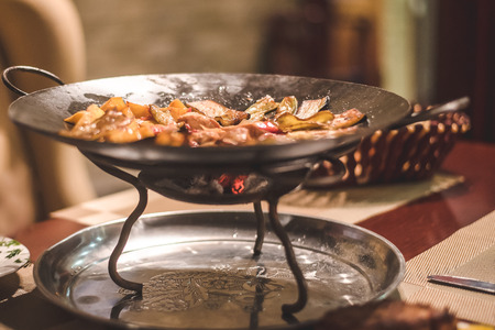 Vegetable stew with meat served in a restaurant in a beautiful metal vase with glowing coals. Eastern cuisine