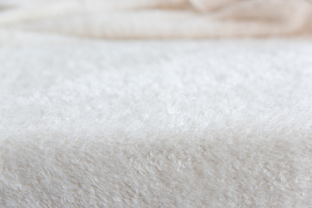 White delicate soft background of plush fabric. Texture of beige soft fleecy blancet