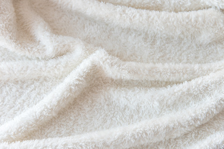 White delicate soft background of plush fabric. Texture of beige soft fleecy blanket textile with twisted folds.
