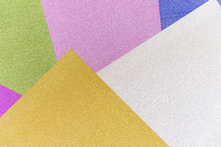 Abstract geometric background of colored paper sheets. Multicolored glitter paper texture.