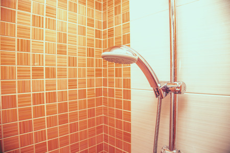 closeup of a height-adjustable shower head  in modern bathroom with orange wall . Copy space Standard-Bild