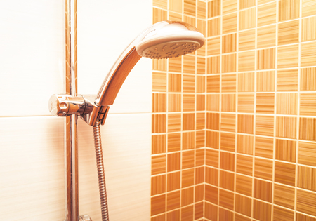 closeup of a height-adjustable shower head  in modern bathroom with orange wall