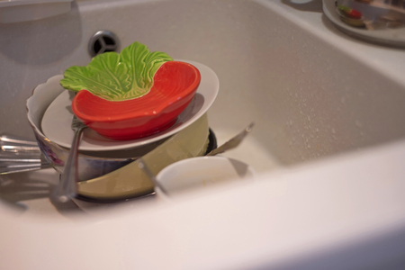 A lot of dirty dishes in the white sink in the kitchen Stock Photo