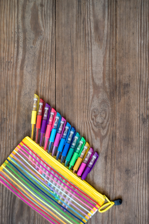 Set of multicolored gel pens on wooden background. School concept. Copy space.