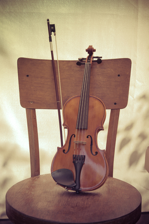 violin and bow, stand on an old wooden chair. Concept art. Retro style toned photo 写真素材