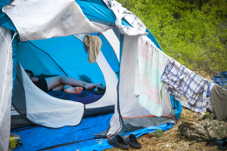 tourist tent camping in forest. Tourist life - clothes are dried, the guitar stands near the tent. Open tent, visible legs of a person resting Stockfoto