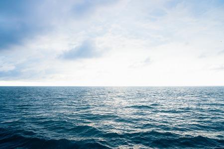 Widok z balkonów kabiny na wzburzone morze i fale od burty statku wycieczkowego. Obraz pejzaż morski. Niebo z chmurami, niewielkie fale na powierzchni morza. Ekscytacja na morzu