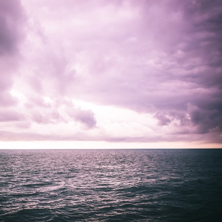 Seascape tinted in purple color picture. The sky with clouds, waves on the sea surface, dark toning abstract photography. View from cabin balconies the rough seas and waves off the side of cruise ship