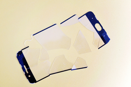 broken safety glass for smartphone on yellow colored paper background