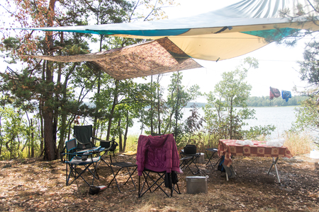 Wilderness Camping Concept . Tourist camp in the forest by the lake. Tourist camp - folding chairs, awning, table,