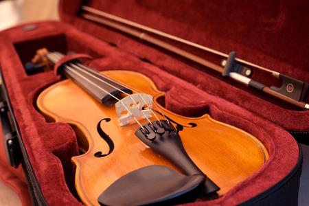 Nahaufnahme von Geige seichte Tiefe des Feldes Geige und Bogen in dunkelrotem Fall. Nahaufnahme von Geigensaiten und Steg Standard-Bild