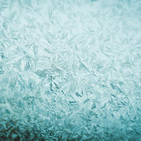 Beautiful gentle graceful frosty pattern on window glass. Texture of frosty patterns.  Blue toned.