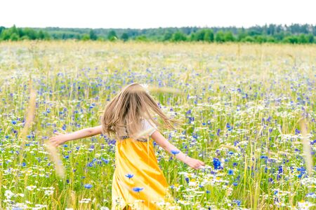 Little pretty girl in yellow Russian dress is dancing on field of wild flowers on summer day. Cute child smiling girl in chamomile field. concept of Russian traditions and folklore.