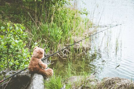 Teddy bear fisherman. Brown teddy bear sits by the lake with a fishing rod and catches fish. Summer nature idyllic landscape