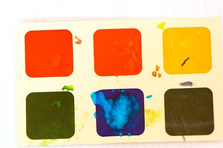 Childrens watercolor paints on cardboard for drawing on white paper background