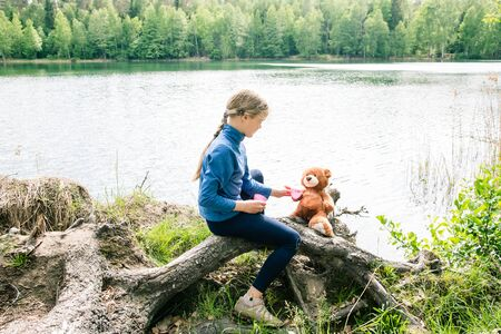 Teddy Bear is a fluffy toy for little cute girl. Every Child love Teddy Bear as their Best Friends hugging and holding together go to Picnic and read book. Best Friend Concept. Warm vintage toning.