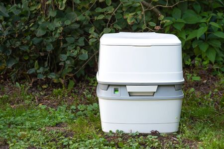 Chemical portable toilet. Single portable toilet standing on a green grass in garden. Horizontal photo.