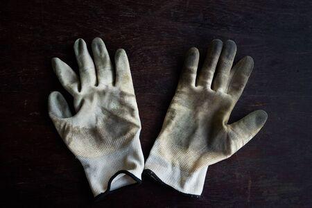 A old dirty textile work gloves on dark wooden background Banco de Imagens