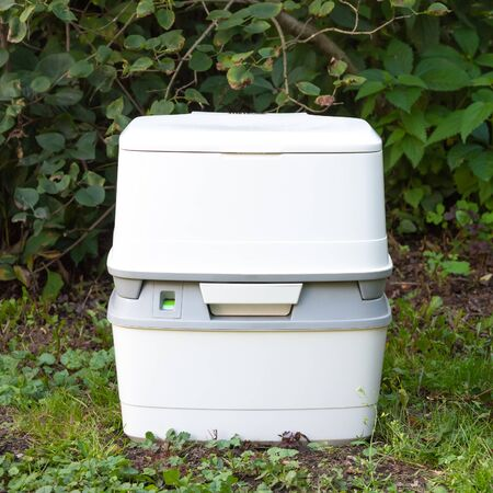 Chemical portable toilet. Single portable toilet standing on a green meadow Standard-Bild