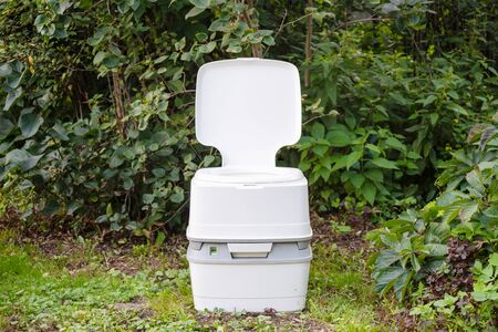 Chemical portable toilet. Single portable toilet standing on a green meadow 版權商用圖片