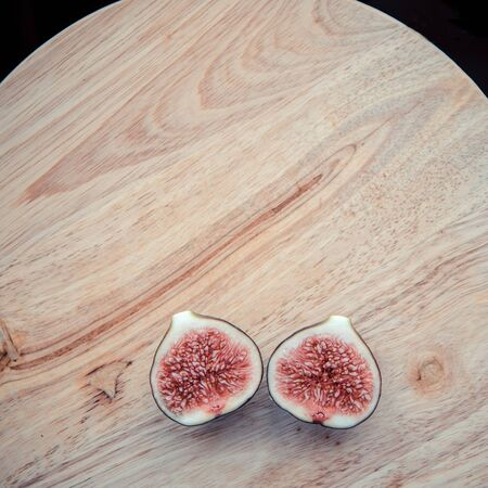 A two cross section figs. One fig sliced in half on on wooden board background. Focus is on the sliced fig. Top view, copy space.