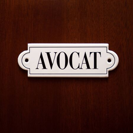 closeup on door with white lawyer name Avocat in french. Concept of lawyer services.