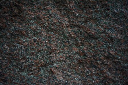 Dark red and black granite background or texture with chipped, unpolished, rough surface stone. High resolution photo