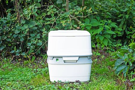 Chemical portable toilet. Single portable toilet standing on a green nature courtyard background