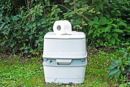 Chemical portable toilet and toilet paper roll. Single portable toilet standing on a green nature courtyard background