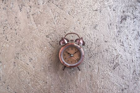 Clock at 10 O clock in the morning with vintage style alarm clock golden wooden background. Windup Type Alarm Clock. Home office. Copy space Imagens