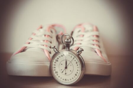 White women's sneakers, shoes for sports, close-up. An apple, a stopwatch and a measuring tape. Concept of fitness, sport, healthy lifestyle. Vintage toned photo, soft selective focus.