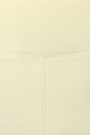 Background with white artificial leather, close up photo image. Photo picture of white eco leather. Coarse - grained texture. Stitched eco-leather seat upholstery.