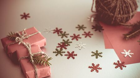 Christmas background with gift boxes, clews of rope, paper and decorations on red. Preparation for holidays. Gift wrapping concept.