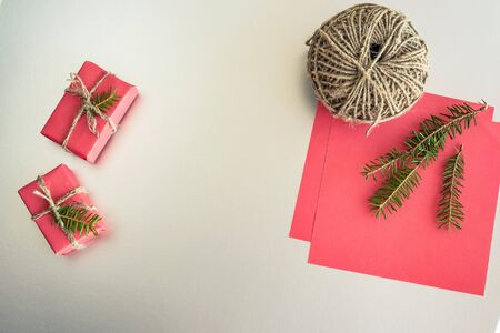 Christmas background with gift boxes, clews of rope, paper and decorations on red. Preparation for holidays. Gift wrapping concept. Top view with copy space.