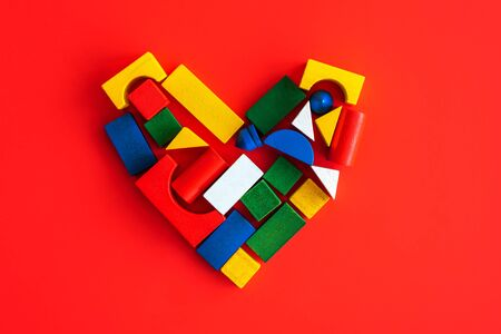 Wooden bright geometric shapes on colorful heart on red, multi colored education toy for kid on red paper background