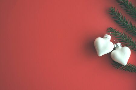 Christmas tree white glass toys two hearts and natural fir branch of spruce on red paper. Concept of love, lovers in christmas Art xmas greeting card. vintage toned. Flat lay, top view, copy space.