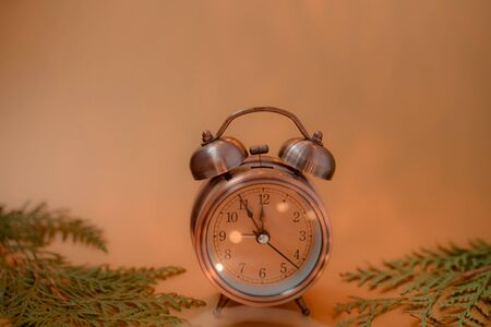 Close up of retro alarm clock on blurred Christmas background with blurred yellow
