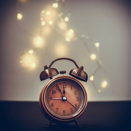 Close up of retro alarm clock on dark background with bokeh Christmas light