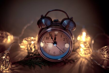 Close up of retro alarm clock on blurred Christmas background with bokeh light garland