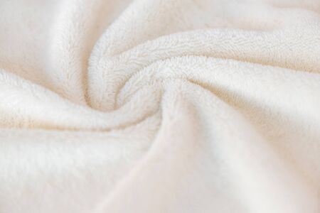 White delicate soft background of plush fabric cozy plaid. Texture of beige soft fleecy blanket textile with twisted beautiful folds.