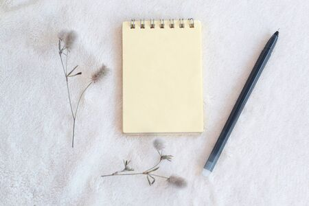 White delicate soft background of plush fabric, on it is a yellow blank notebook with a spiral for notes, pen, fluffy flower Banco de Imagens