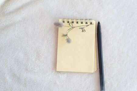White delicate soft background of plush fleecy fabric, on it is yellow blank notebook with a spiral for notes, pen, fluffy flower