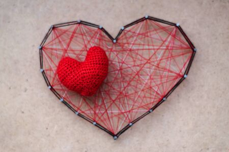 Small knitted heart lies on big red heart made of threads, stranded between the nails. The concept of great nascent or hidden love. Banco de Imagens