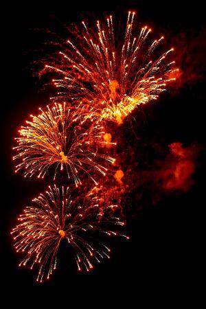 Gros plan d'artifice festif rouge et or sur fond noir. Abstrait de vacances