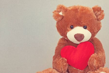 Valentines Day. Teddy Bear hugging red heart. Vintage retro romantic style. Unusual creative greeting card. Family, wedding and friendship
