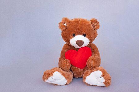 Valentinstag. Teddybär, der rotes Herz umarmt. Retro-romantischer Stil der Weinlese. Ungewöhnliche kreative Grußkarte. Familie, Hochzeit und Freundschaft Standard-Bild